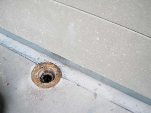 This is a poor deck drain location, as it is next to a wall within a perimeter flashing detail.