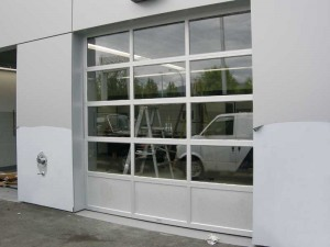 This is a different style of an aluminium overhead door where the bottom panels are insulated and have a 'kick-proof' design. The bottom section absorbs the impact of the door closing, reducing any jarring of the glazing in the above panels.