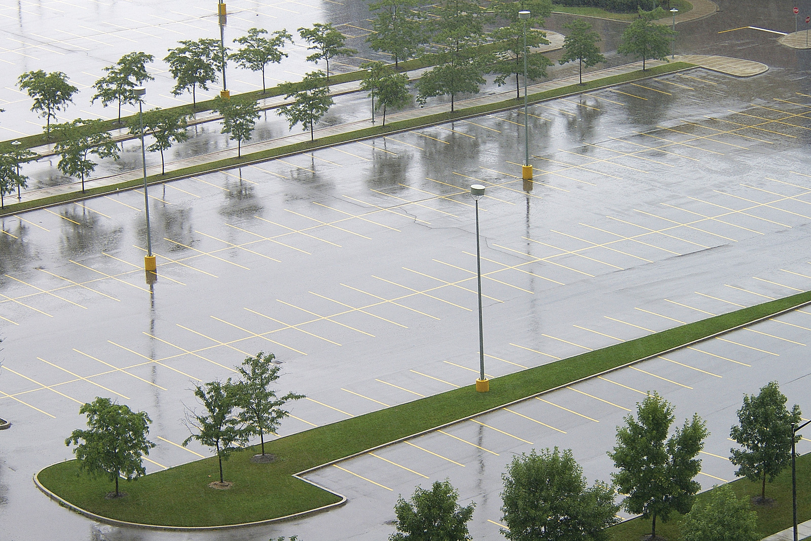 In a traditional concrete parking lot, rainwater can pond and/or become runoff thanks to the hardscaping. The result is a negative impact on the natural environment and storm sewers that struggle to keep up with the added loads. Photo © BigStock/David Wood