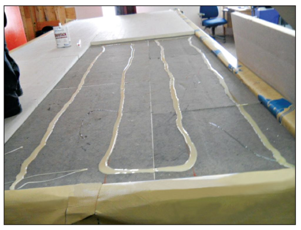 The photo below and at right depict another step in the AARS system preparation for the CSA A123.21 test: asphalt-based cover board adhered on insulation board.