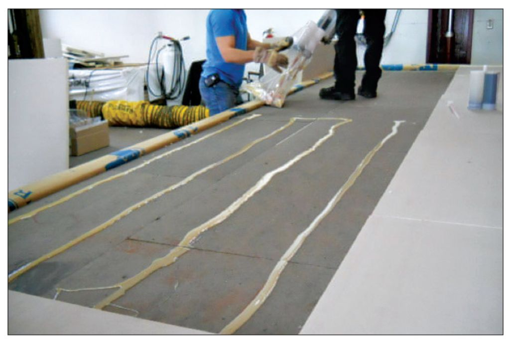 The photos depict another step in the AARS system preparation for the CSA A123.21 test: asphalt-based cover board adhered on insulation board.