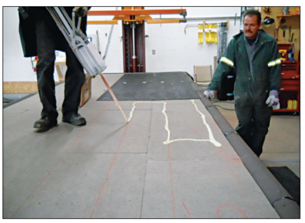 Asphalt-based cover board adhered on the insulation board for the CSA A123.21 test protocol.