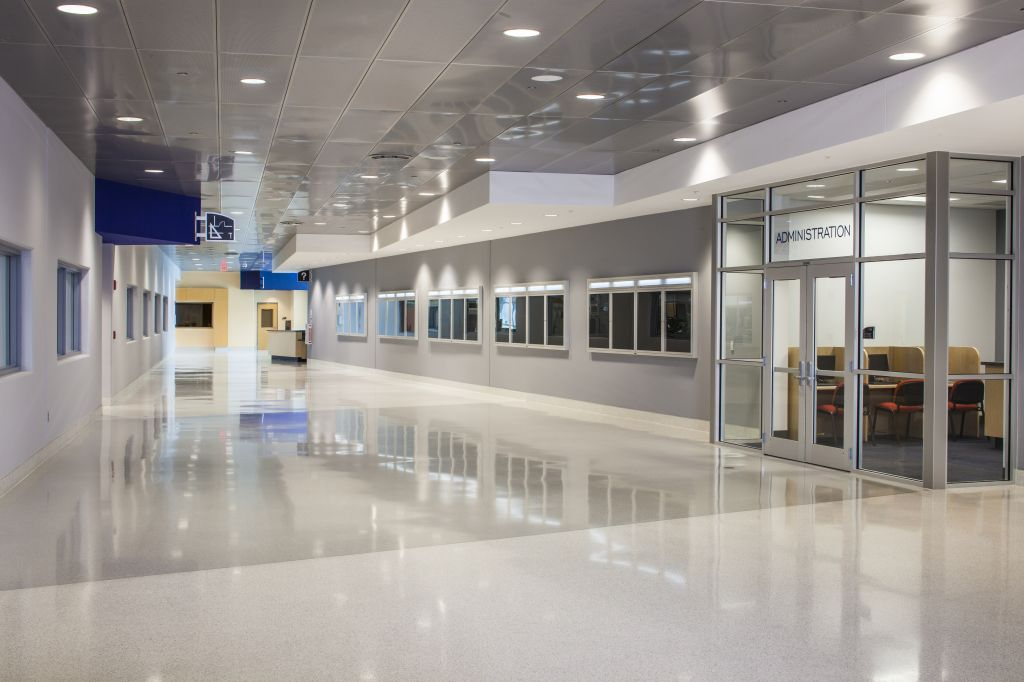 In large multi-purpose spaces with expansive hard surfaces, perforating the metal ceiling panels and adding an acoustic backer can help manage the reverberation and improve sound quality.