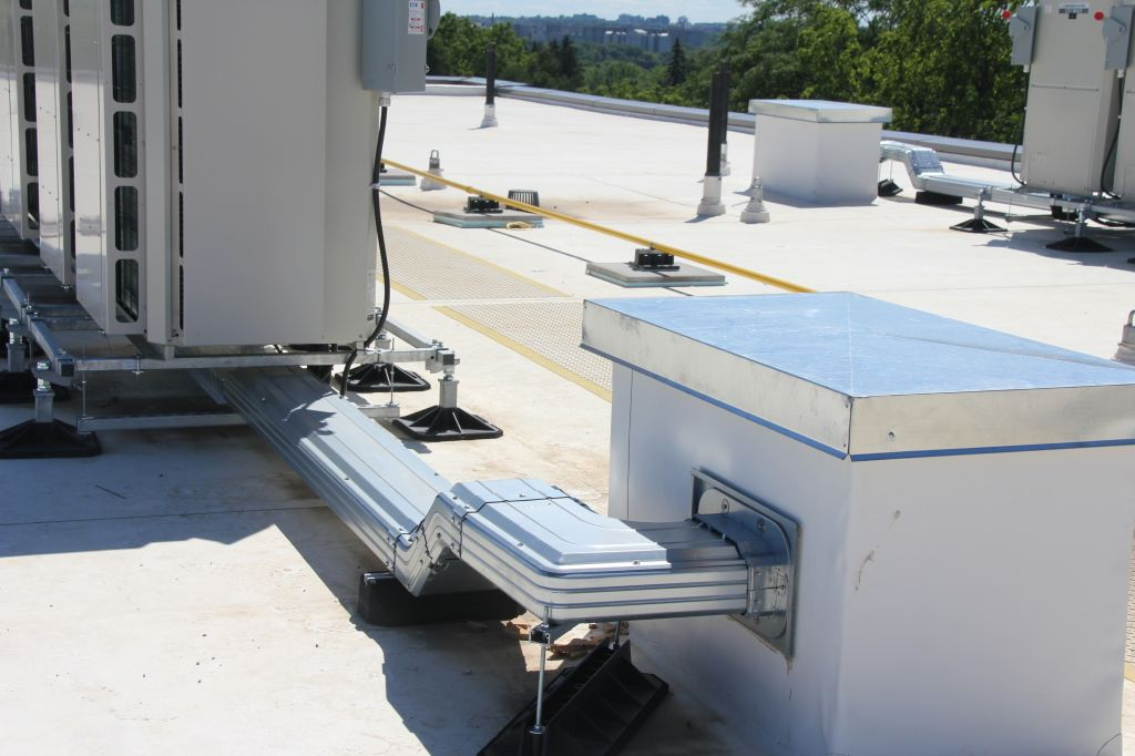 London, Ont.'s Brescia University College residence hall and dining complex's rooftop modular steel mounting frame system supports variable refrigerant flow (VRF) condensers as well as the lineset protection duct manufactured out of corrosion and scratch-resistant zinc/aluminum/magnesium (ZAM)-coated metal duct to preserve lineset insulation and its thermal transfer functions. Photo courtesy Baymar Supply.