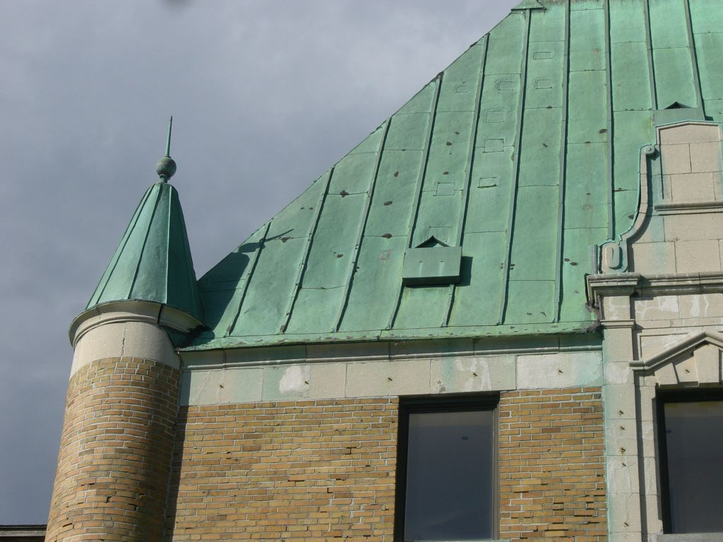 A close-up shows punch points in the batten-seam panels where the copper roof was deformed during ice storms.