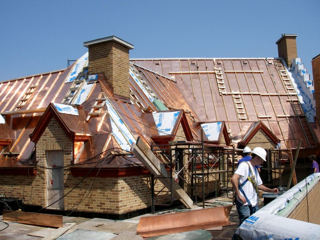 Sheet metal workers installing batten seam copper roofi ng.