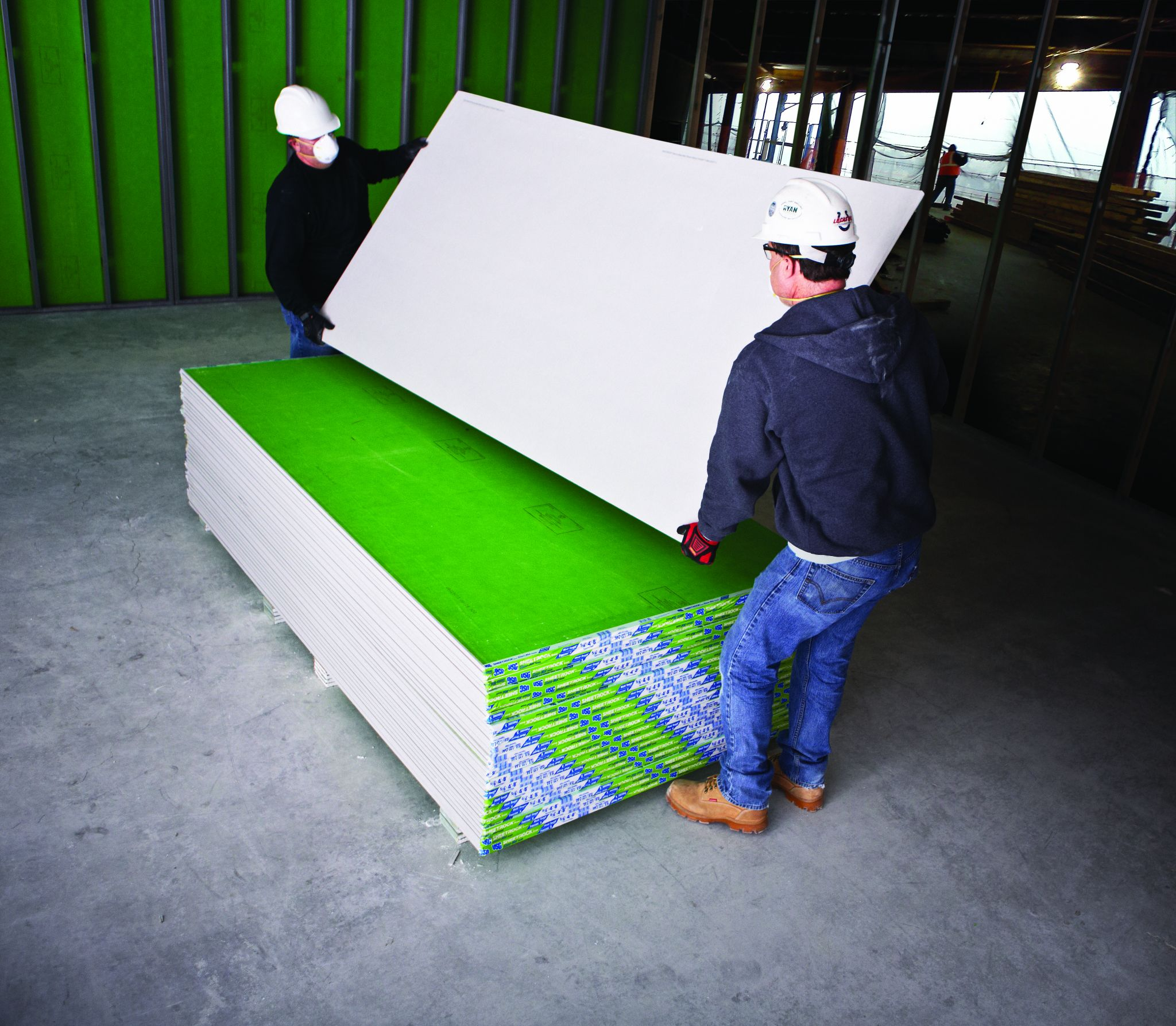 Pictured above are two workers handling glass-mat water and mould-resistant interior gypsum panels during the pre-dry-in installation process. Photo courtesy USG