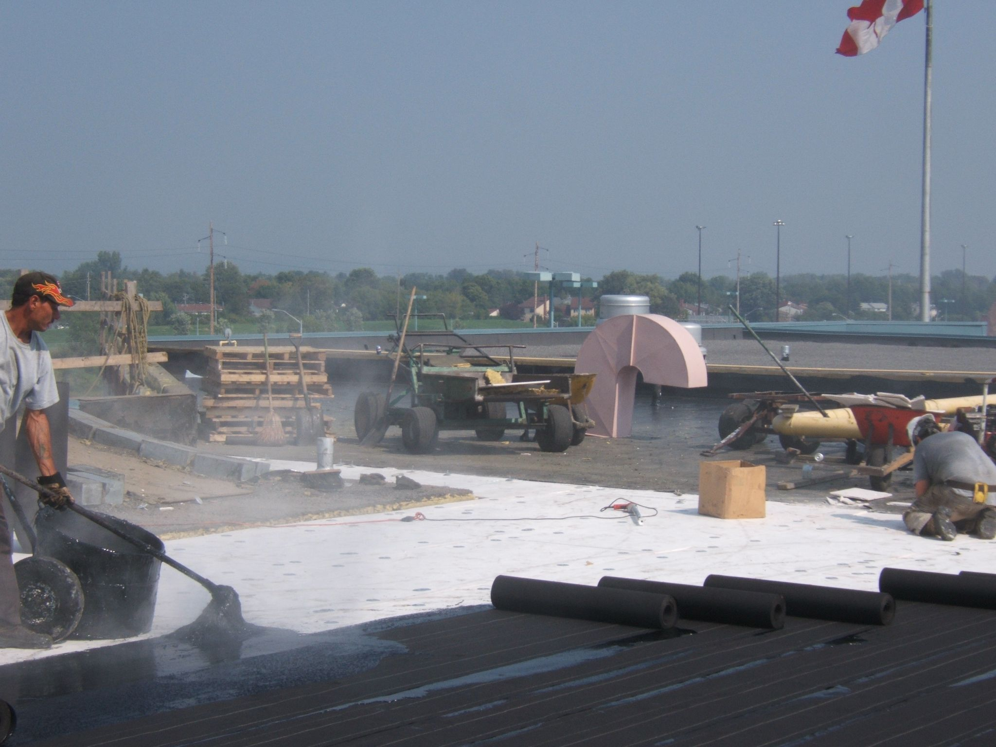 A typical application of 'gang-rolled' felts being applied by hand mopping. The four plies are applied quickly and accurately. This method is ideal for roofing large open areas where penetrations are of little concern.
