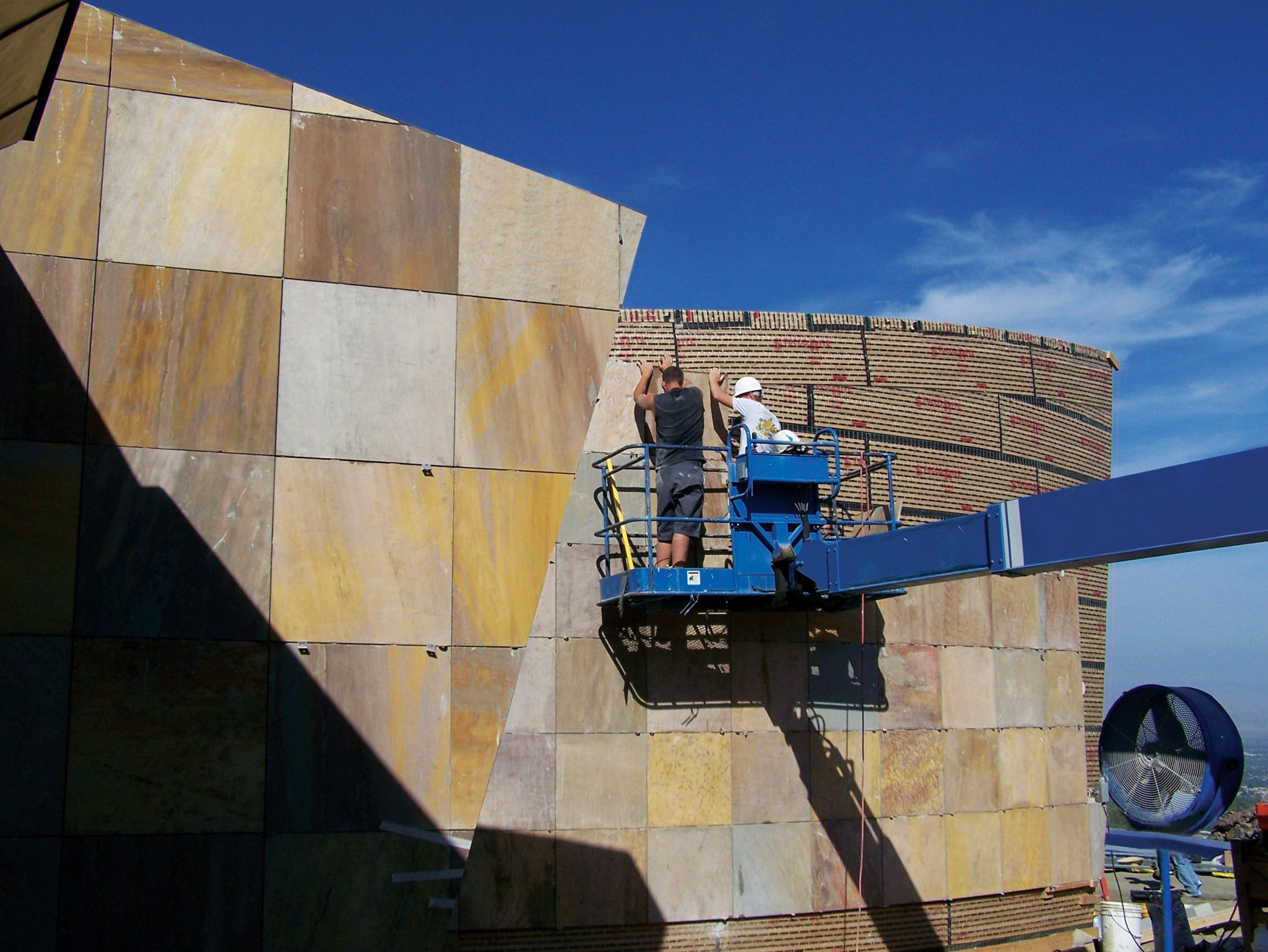 These workers are using a manlift to mechanically anchor sandstone to a building's exterior wall with metal angle clips.
