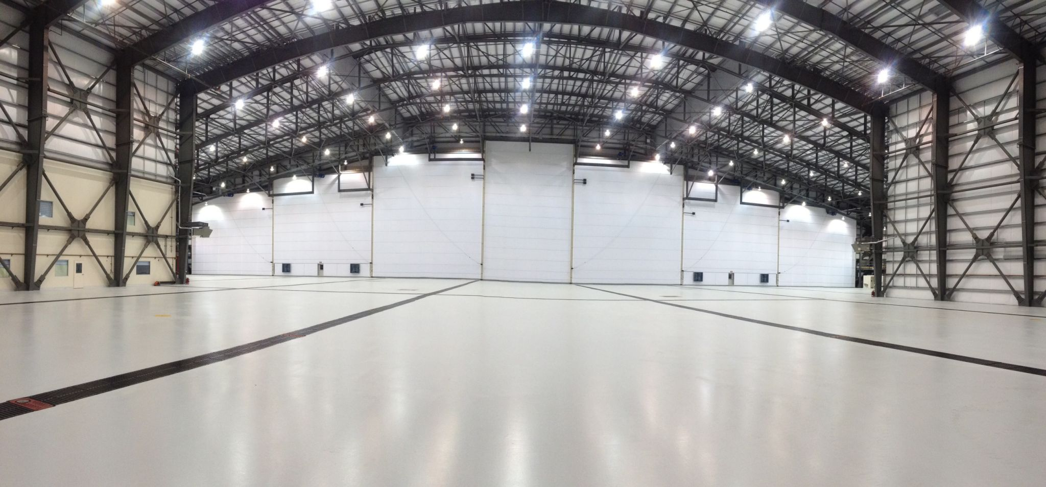 The fabric system seen here in an aviation hangar can accommodate very wide openings and variable heights. The system is made of numerous curtains with vertical mullions that swing up creating a natural opening to suit the width of the wingspan. These door systems are also used in large industrial facilities with translucent fabric enhancing the interior of truck shops and other such buildings.