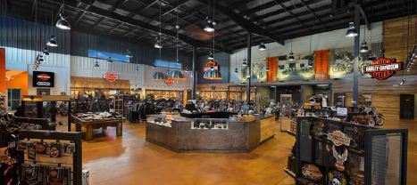 The showroom features high ceilings with a mix of hard and soft design elements. Steel is tempered by warm colors, including the signature Harley-Davidson orange. The walls also incorporate wood planks.