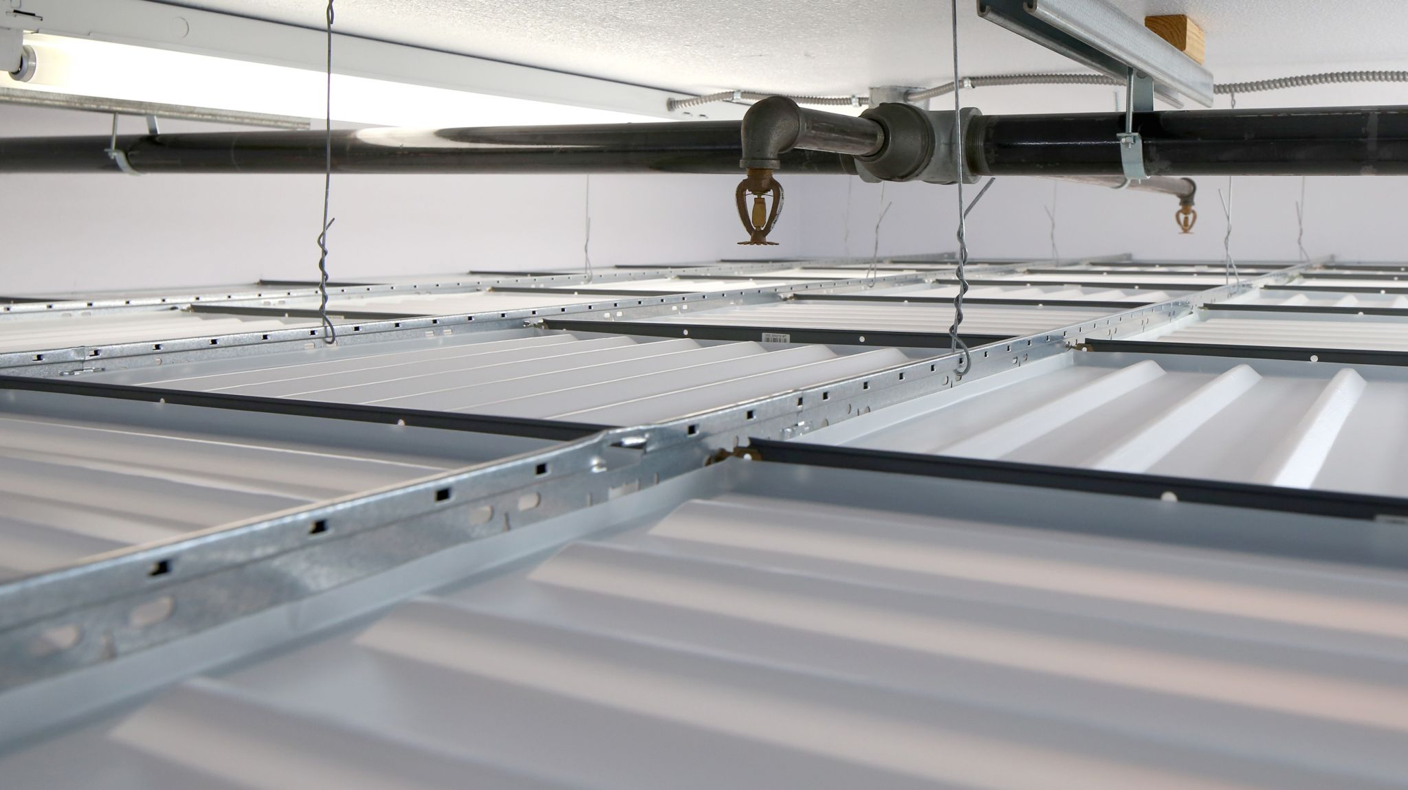 Drop out ceiling panels installed beneath fire sprinklers