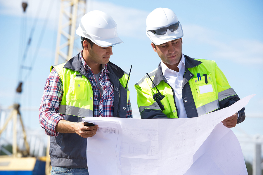Two engineers at construction site are inspecting works on site according to design drawings. Photo © BigStockPhoto