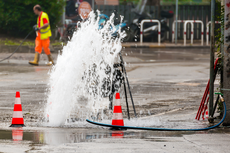 Road Spurt Water Beside Traffic Cones And A Technician In Backgr