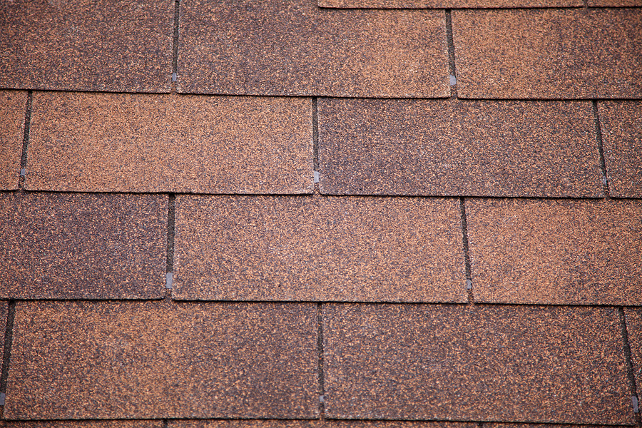 A close-up of brown toned architectural style asphalt roofing shingles.