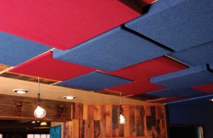 Ceiling-mounted panels of varying depths provide broad-spectrum sound absorption and diffusion.