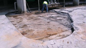 The photo above shows the beginning of a concrete topping slab removal in order to replace a failed peel-and-stick waterproofing membrane. Deck construction did not incorporate a drainage layer at the membrane level, which led to premature failure.