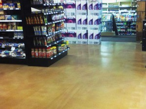 The floor of this supermarket in Whistler, B.C., is a fast-curing cementitious overlay. The as-poured surface was not ground or otherwise mechanically or chemically profiled. It was dyed, densified, and burnished. It was treated with silica-polymer dispersion stain protector and burnished again to a reflective shine.