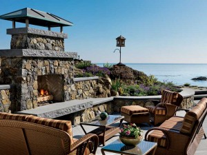 The outdoor fireplace and patio are made from natural stone. Natural stone copings cover the stone walls, and natural stone slabs were used for the hearth.