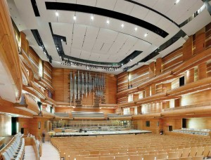 The hall has three balconies, and audience seating wraps around the stage. The top of the room is crowned by multi-part suspended motorized sound reflectors. Photo © Tom Arban