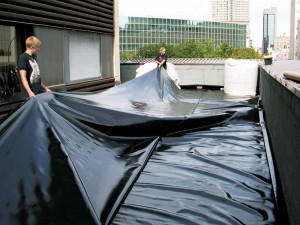 The landscapers install a root barrier to protect the roof membrane from root damages.