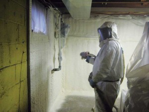 Closed-cell SPF being applied to concrete in a basement.