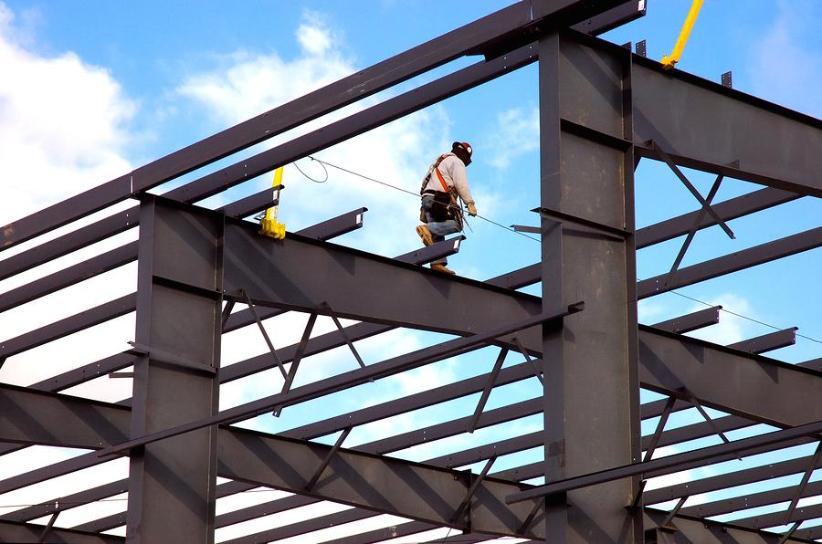 Structural steel worker walking on girders roof