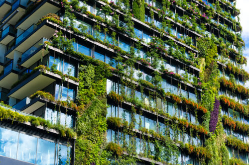 Green skyscraper building with plants growing on the facade. Ecology and green living in city urban environment concept. Park in the sky One central park building Sydney Australia