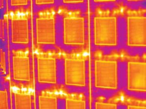 Prefabricated wall panels can expedite construction. However, tie-ins between panels must still be carefully treated to prevent systemic issues such as air leakage, shown in this thermographic scan. This close-up shows air leakage at panel joints.