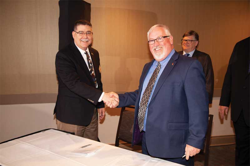 CSC president David Boyle, CTR, and CSI chair Ron Geren, FCSI, sign an updated MasterFormat licensing agreement.