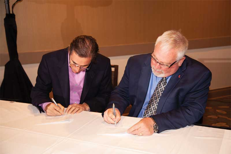 Building Systems Design (BSD) CEO Chris Anderson and CSC president David Boyle, CTR, officially sign the deal that will see the two jointly provide the Canadian National Master Specification (NMS) via new and improved website, www.specmarket.com.