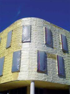 Spray foam conforms directly to the surface it is being applied to regardless of shape, geometry, or irregularities. This ability applies if used on either side of an exterior wall. Medium-density spray foam can only be employed on the exterior as shown for this building.