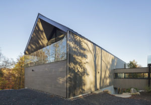 It houses two superimposed garages, a workshop, a large creative room, and a mezzanine.
