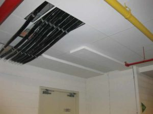 A service penetration affecting an acoustical ceiling.