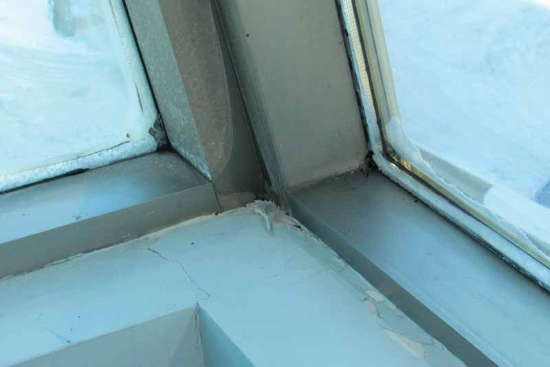 Figure 1: Formation of condensation and ice on interior curtain wall surfaces (background) and damage to interior wall finishes at a 12-storey office building in Québec.