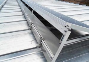 A standing-seam roof where racking has been clipped over the ridges, resulting in a fixed system with no roof penetrations.