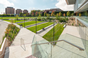 A natural amphitheatre was created at York University (Toronto), extending the indoor realm into the environment with grass slopes, natural stone seating, and an escarpment wall. Images courtesy FORREC