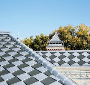 Combining interlocking roof tiles of zinc ASTM B69-16, Standard Specification for Rolled Zinc, Type 2 alloys in pre-patinaed blue-grey and graphite-interlocking roof tiles can create a checkerboard esthetic.