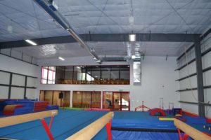 A view from the gym floor, facing the viewing areas on the main floor and the mezzanine.