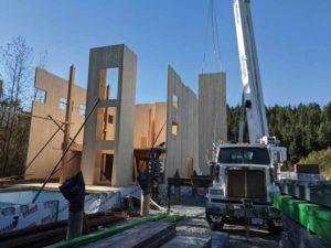 The cross-laminated timber (CLT) wall panels of the Whistler Community Services Society (WCSS) building in B.C., together with the elevator and stair cores, run from grade beam to eaves, as in balloon frame construction. The panels were lifted off the truck and lowered directly into place. Photo courtesy Fast + Epp