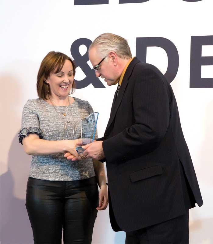 Debroah Bryne receives her award from Construction Canada's editorial director Blair Adams.