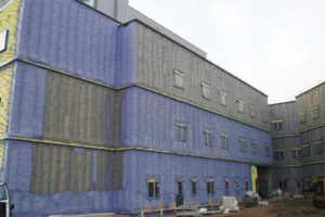 Spray foam insulation applied on glass mat gypsum board as continuous cavity wall insulation on the exterior of a hospital.