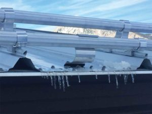 Bar or fence- styled snow guards can be attached to standing-seam roofs with clamps or attached to exposed, fastened roofs via screws.