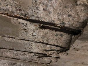 Structural deterioration as a result of a failure of the podium deck waterproofing system.
